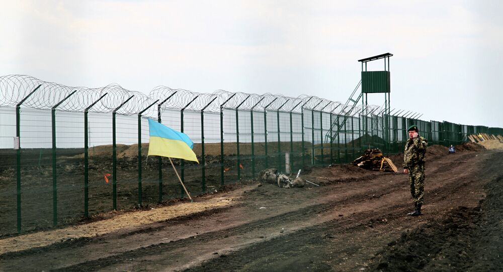 A Ukrainian border guard officer speaks on a phone near a national flag attached to the fence on the Ukrainian-Russian border near Hoptivka, Kharkiv region, eastern Ukraine