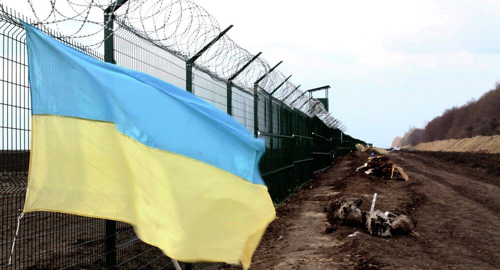 A Ukrainian national flag is attached to the fence on the Ukrainian-Russian border near Hoptivka, Kharkiv region, eastern Ukraine