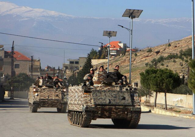 Lebanese army troops drive armoured personnel carriers (APC) in the village of Ras Baalbak in the eastern Bekaa Valley near the border with Syria during clashes between Islamist fighters and Lebanese troops on Jananuary 23, 2015