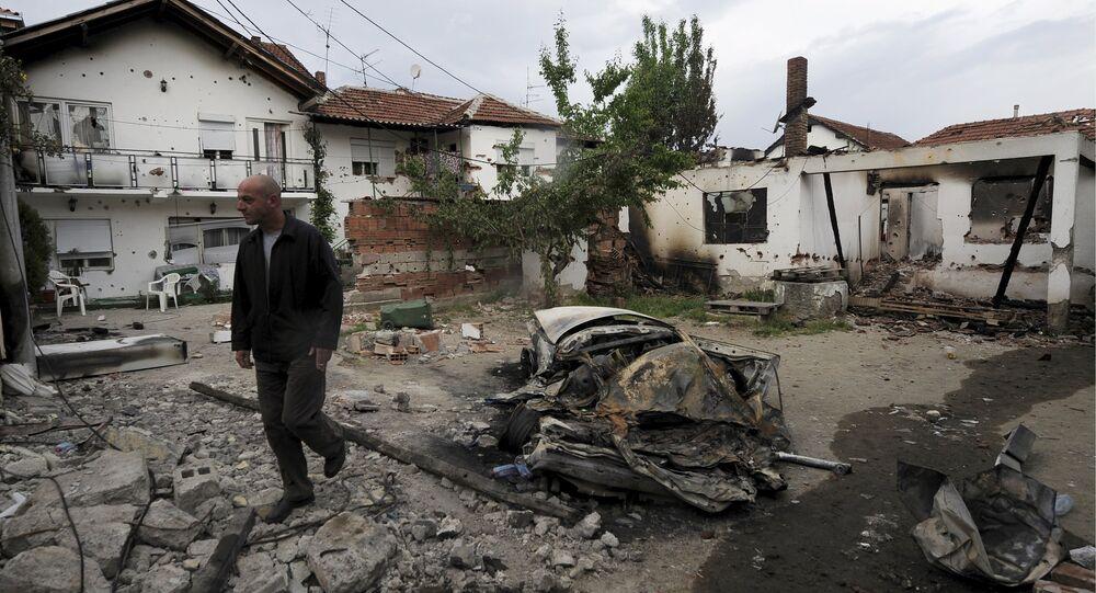 A man walks through a damaged house in Kumanovo, Macedonia May 11, 2015