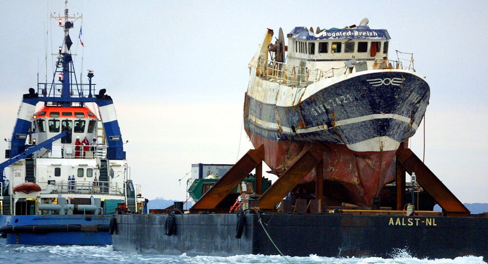 A picture taken on July 13, 2004 shows the wreckage of French trawler Bugaled Breizh, installed at a barge, as it is being towed, and escorted by military ships, towards a French military port of Brest.file photo
