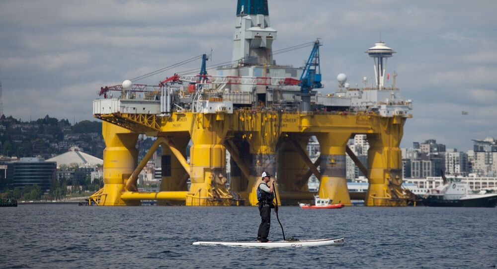 A man on a stand up paddle board is seen in front of the Shell Oil Company's drilling rig Polar Pioneer along the Puget Sound in Seattle, Washington, May 14, 2015