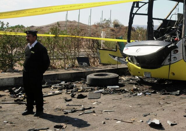 An Egyptian policeman stands guard next to wreckage of a bus that was targeted the day before by a bomb in the Egyptian south Sinai resort town of Taba on February 17, 2014