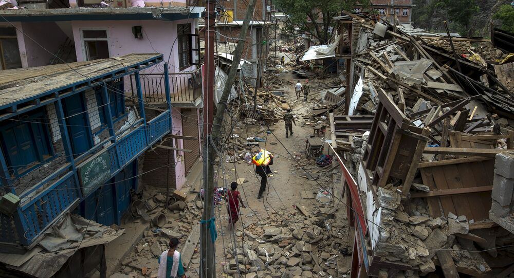 Local residents walk past collapsed buildings after Tuesday's earthquake at Singati Village, in Dolakha, Nepal, May 15, 2015