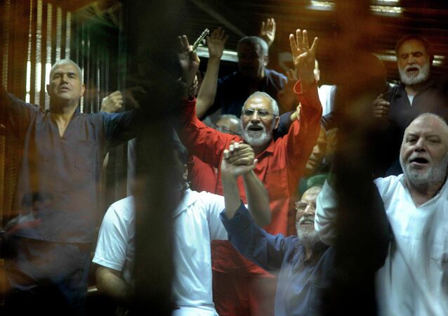 Egyptian defendants including the spiritual leader of the Muslim Brotherhood, Mohammed Badie, center, make a four-fingered gesture referring to the 2013 killing of Muslim Brotherhood protesters at the Rabaah Al-Adawiya mosque