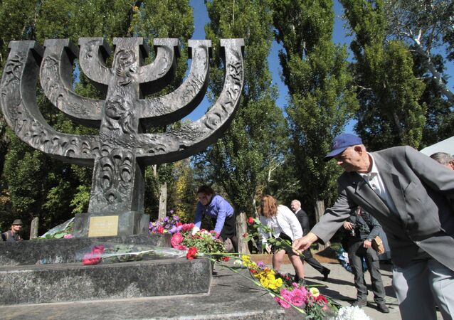 People lay flowers at the monument at the Babi Yar national historical and memorial park during a commemorative rally.