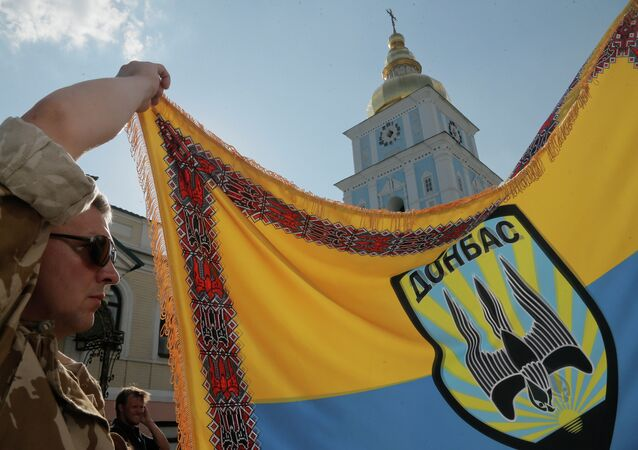 An officer of volunteer battalion 'Donbas' holds battalion colours during a blessing ceremony in St. Michael Cathedral in Kiev, Ukraine, Tuesday, Aug. 19, 2014