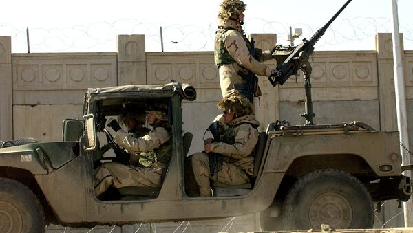 US soldiers from the 1st Battalion, 22nd Regiment of the 4th Infantry Division, ride on a military vehicle as they leave their base on a mission in Tikrit, 180 Kilometers (110 miles) north of Iraqi capital Baghdad, 30 December 2003. - Sputnik International