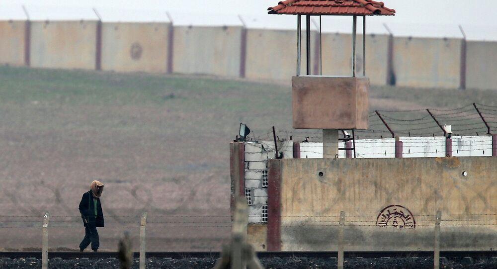 An armed man walks across the Turkish Akcakale border gate