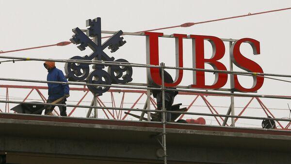 Workers are seen beside a logo of Swiss bank UBS in Zurich - Sputnik International