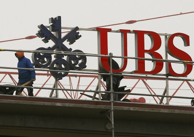 Workers are seen beside a logo of Swiss bank UBS in Zurich