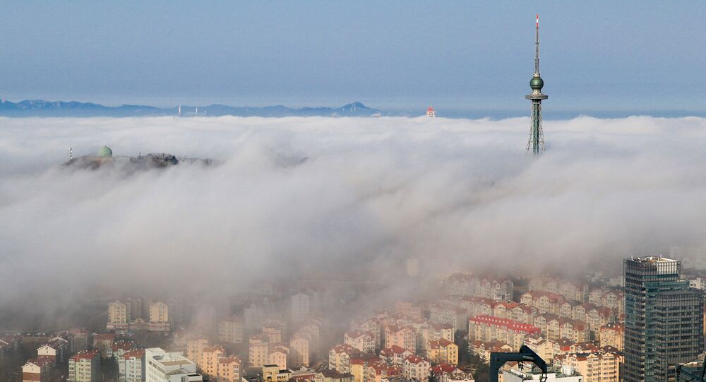 Residential buildings are seen among fog in Qingdao, Shandong province, China
