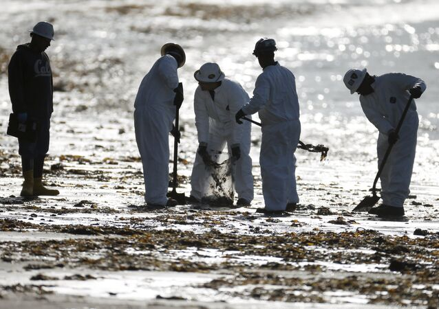 Workers clean up an oil slick along the coast of Refugio State Beach in Goleta, California, United States