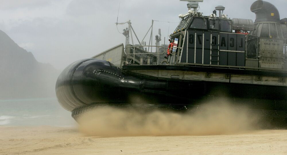 A U.S. Navy Landing Craft Air Cushion (LCAC) amphibious vehicle storms the beach at Bellows Air Force Station on Oahu, Hawaii.