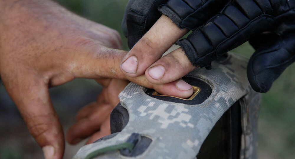 A US soldier records finger prints of a man while on patrol in Afghanistan.