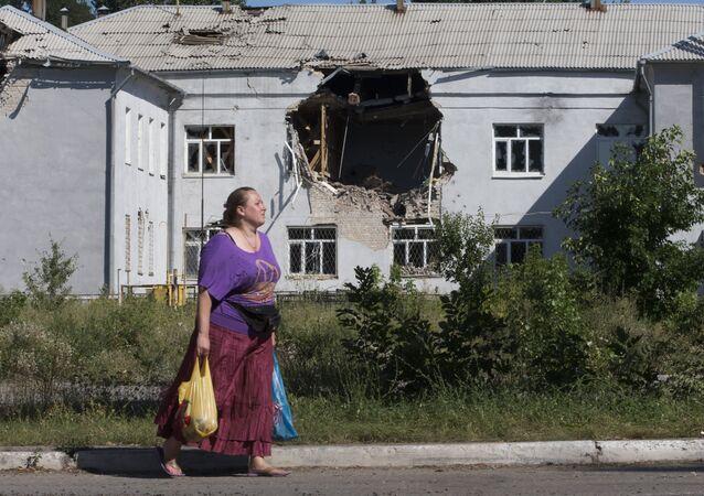 A woman walks past a damaged school in the city of Lisichansk, Luhansk region, eastern Ukraine