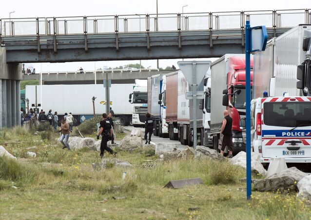 Policemen stand guard next to truck queuing to board a ferry to Great Britain to prevent migrants to reach the UK illegally, on September 10, 2014 in the French port of Calais