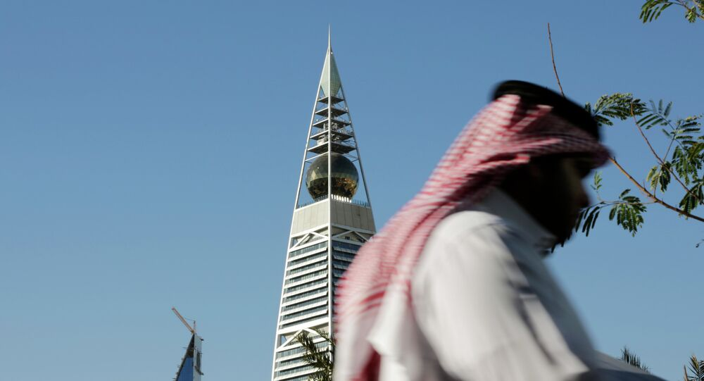 A Saudi man passes the al-Faisaliya tower in Riyadh, Saudi Arabia.