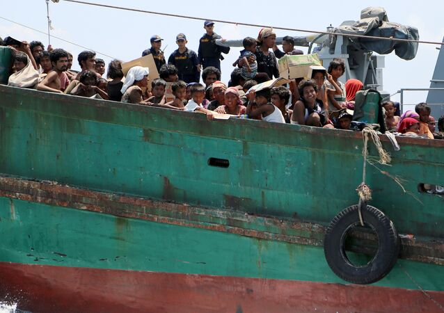 Navy officers look at migrants on their boat being towed away from Thailand by a Thai navy vessel, in waters near Koh Lipe island May 16, 2015