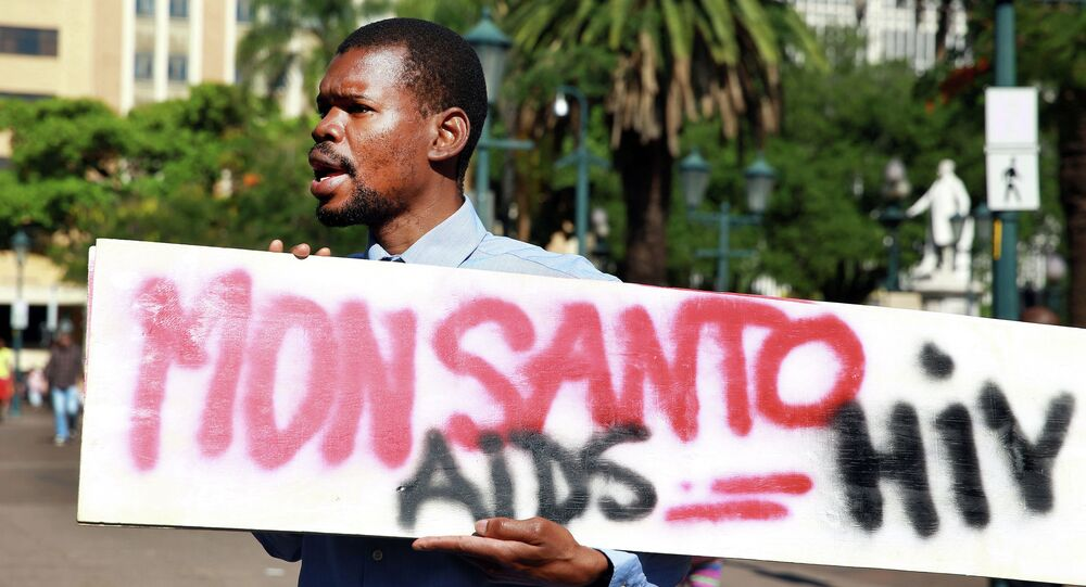 An activist carries a sign during a protest against chemical giant Monsanto in Durban on May 24, 2014