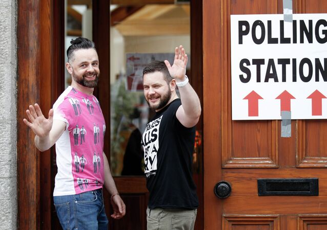 Partners Adrian, left and Shane, arrive to vote at a polling station in Drogheda, Ireland, Friday, May 22, 2015