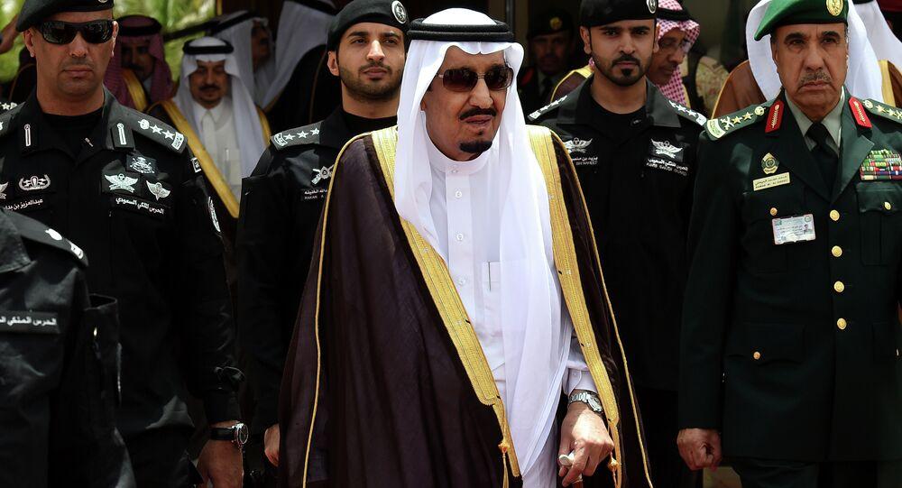 Saudi King Salman bin Abdulaziz (C) walks surrounded by security officers