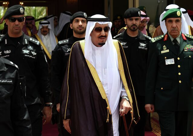 Saudi King Salman bin Abdulaziz (C) walks surrounded by security officers