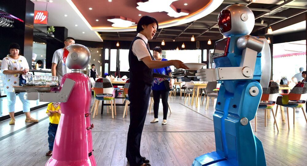 A waitress places dishes on a tray carried by a robot couple at a restaurant in Jinhua, Zhejiang province, China, May 18, 2015