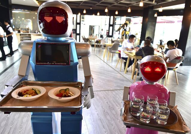 Robot couple Xiaolan (L) and Xiaotao carry trays of food at a restaurant in Jinhua, Zhejiang province, China, May 18, 2015