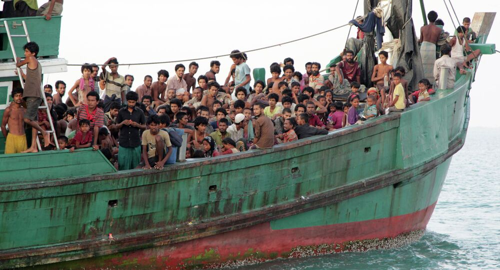 May 20, 2015 file photo, migrants sit on their boat as they wait to be rescued by Acehnese fishermen on the sea off East Aceh, Indonesia