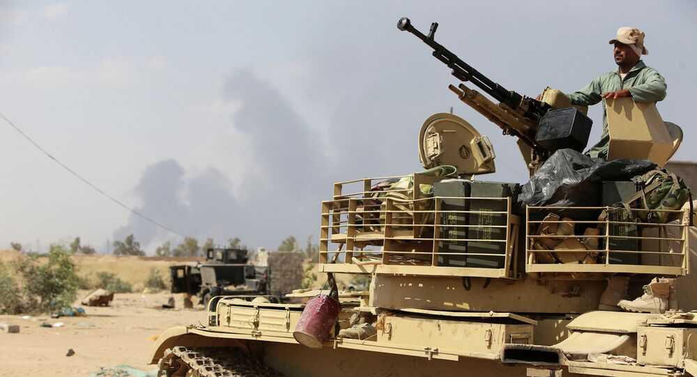 An Iraqi army member mans a tank on the outskirts of Baiji refinery north of Tikrit, during a joint operation between the army and popular mobilisation units to retake the remaining area of the Baiji oil refinery from Islamic State (IS) group jihadists, on May 24, 2015