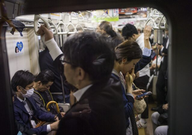 A woman reads on her smartphone while riding the subway in Tokyo on May 12, 2015