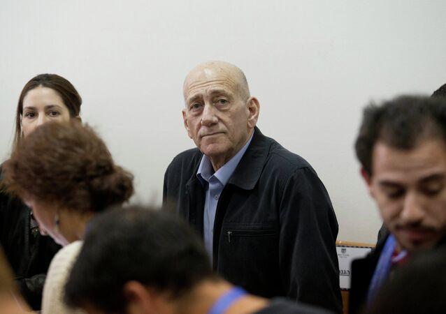 Former Israeli Prime Minister Ehud Olmert, center, waits for a verdict in Jerusalem's District Court on Monday, March 30, 2015