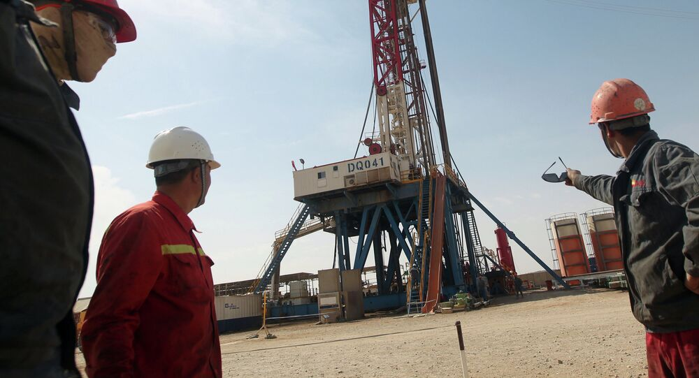 Gazprom employees look at a drilling platform for Gazprom company. File photo