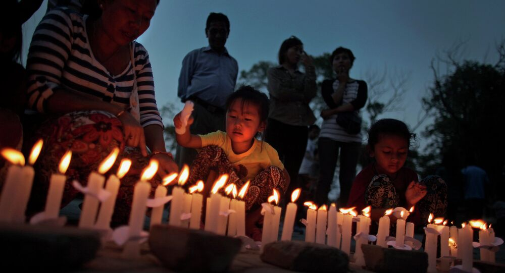 Nepalese people light candles during a candlelight vigil to mark the one month anniversary of the deadly magnitude-7.8 earthquake in Kathmandu, Nepal, Monday, May 25, 2015