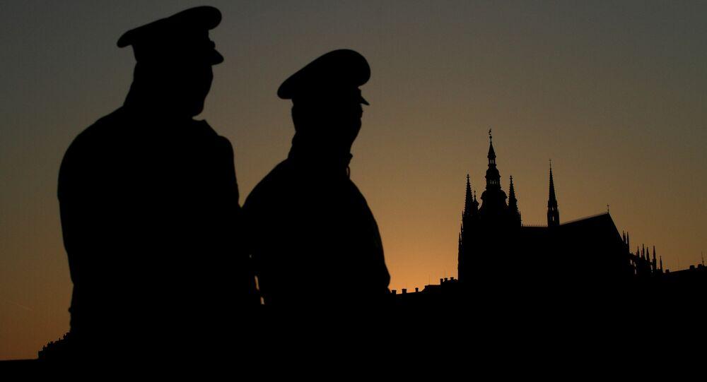 Czech policemen stand guard backdropped by Prague's castle