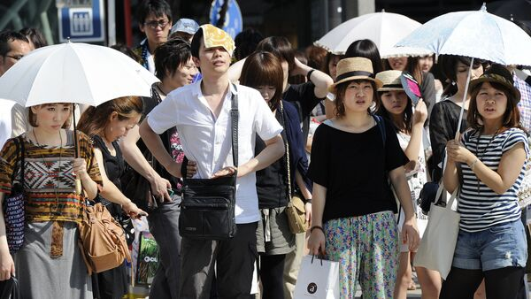 People wait for a green light at a crossing as they use umbrellas and hats to shade themselves from the sunshine in Tokyo - Sputnik International