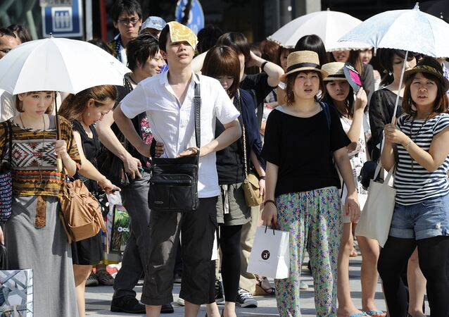 People wait for a green light at a crossing as they use umbrellas and hats to shade themselves from the sunshine in Tokyo