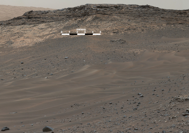This view southeastward from Curiosity's Mast Camera (Mastcam) shows terrain judged difficult for traversing between the rover and an outcrop in the middle distance where a pale rock unit meets a darker rock unit above it