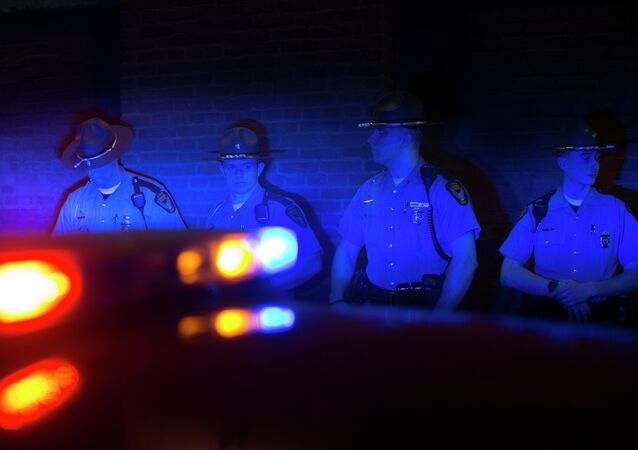 Police officers are illuminated by patrol car lights during a protest against the acquittal of Michael Brelo, a patrolman charged in the shooting deaths of two unarmed suspects.