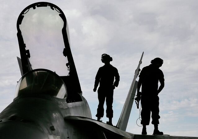 US Marines work atop an F/A-18 at the 309th Aerospace Maintenance and Regeneration Group boneyard in Tucson, Ariz