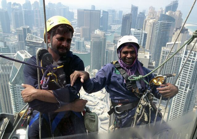 Pakistani window cleaners work on the facade of a building in the Gulf emirate of Dubai