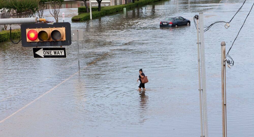 A woman walks in the flood waters in southwest Houston, Texas May 26, 2015