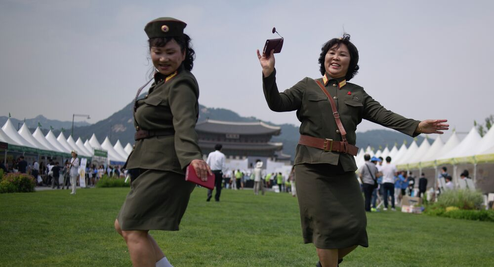 North Korean defectors wearing North Korean military uniforms dance in Gwanghwamun square during a 'unification expo' in central Seoul on May 29, 2015