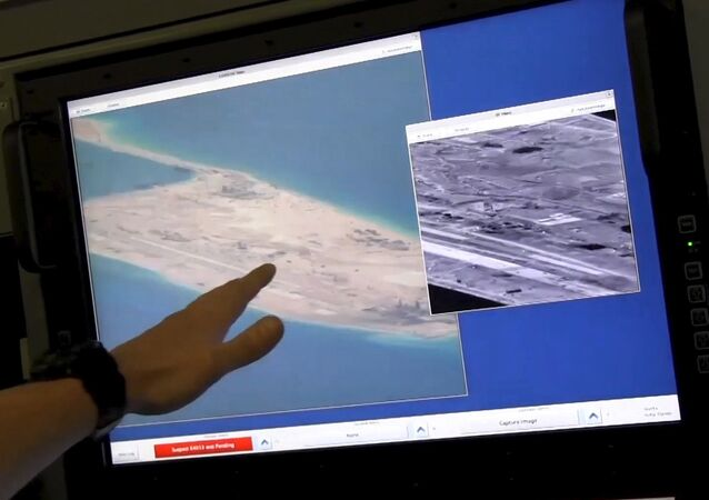 US Navy crewman aboard a P-8A Poseidon surveillance aircraft points to a computer screen purportedly showing Chinese construction on the reclaimed land of Fiery Cross Reef in the disputed Spratly Islands in the South China Sea in this still image from video provided by the United States Navy May 21, 2015