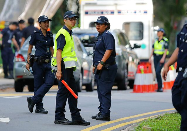 Singapore policemen secure an entry point as they stop pedestrians and attendees of the 14th International Institute for Strategic Studies Shangri-la Dialogue, or IISS, Asia Security Summit, from entering the vicinity, Sunday, May 31, 2015, in Singapore