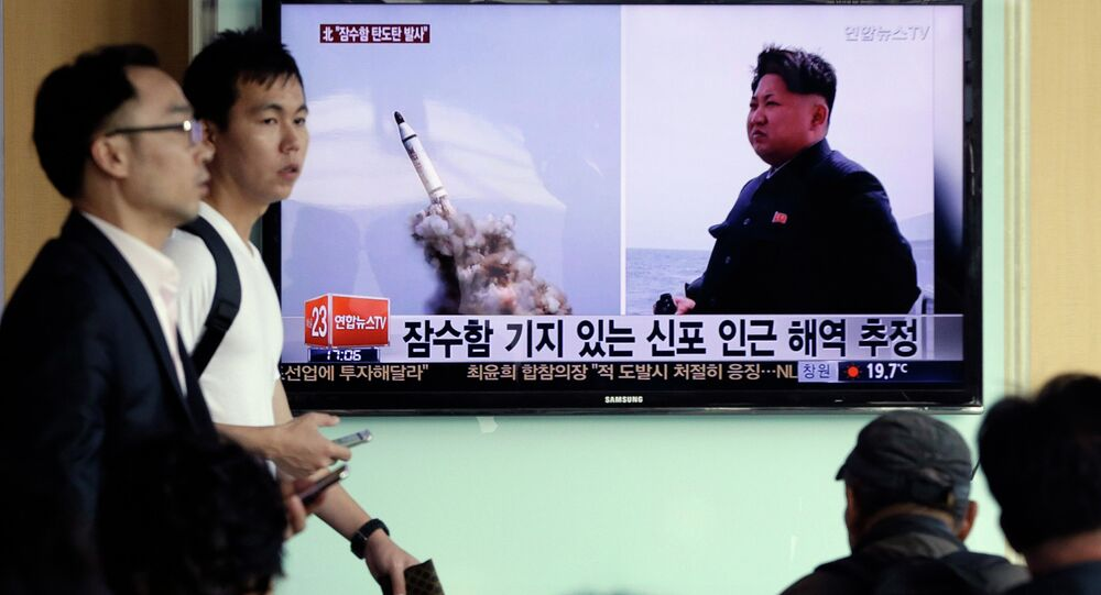 File Photo: South Korean men pass by a TV news program showing images published in North Korea's Rodong Sinmun newspaper of North Korea's ballistic missile believed to have been launched from underwater and North Korean leader Kim Jong-un, at Seoul Railway station in Seoul, South Korea, Saturday, May 9, 2015