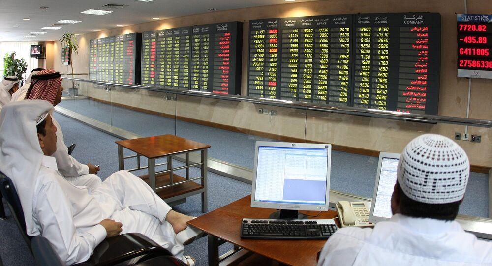 Investors follow the stock market activity on monitors at the Doha Securities Market