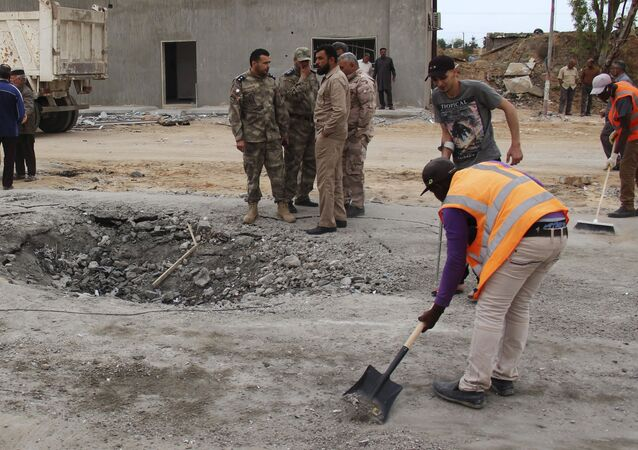 Workers clean the ground after a suicide car bomber blew himself up at a checkpoint in Dafniya outside Mistrata, Libya May 31, 2015