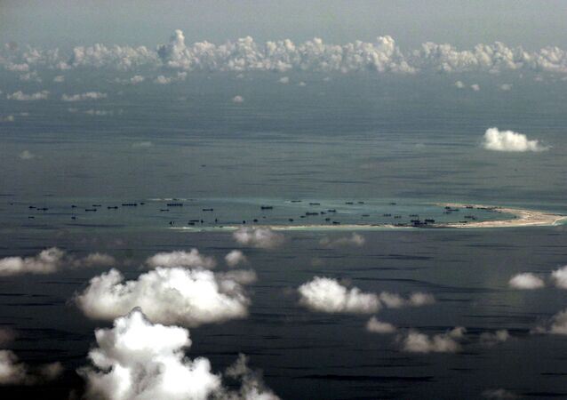 An aerial file photo taken though a glass window of a Philippine military plane shows the alleged on-going land reclamation by China in the South China Sea, west of Palawan, Philippines, May 11, 2015